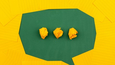 A green speech bubble with yellow elipses made of scrunched-up post-it notes.